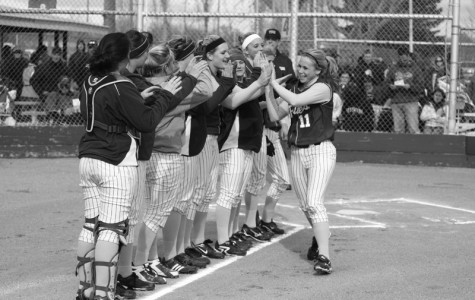 Junior Jenni Peer high-fives her teammates prior to the April 28 cross-town game.