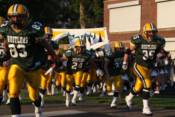 The+Rustlers+charge+out+to+meet+the+Butte+Bulldogs+Aug.+26+at+Memorial+Stadium.