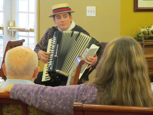 Freshman entertains Cambridge Place residents, spreads holiday cheer with accordion melodies