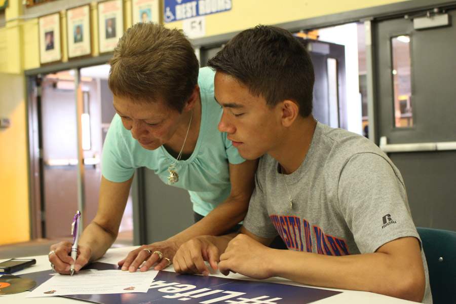 Senior wrestler Deven Altenburg-Lasher and his mom, Brenda Altenburg, sign the paperwork for the wrestling program at the University of Mary on May 11.