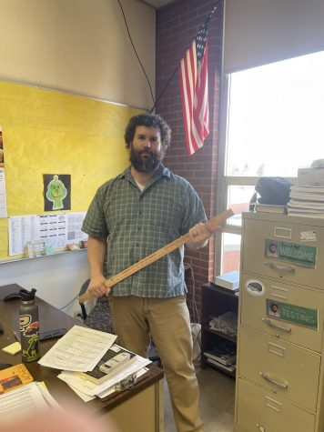 "Teacher Jeremy Comstock holds the ""Needle of Fate,"" the meter stick which he spins atop a stool to select students for various activities."