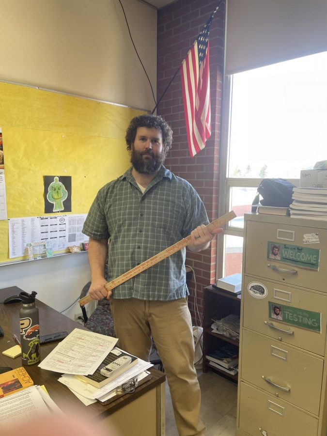 Teacher+Jeremy+Comstock+holds+the+%22Needle+of+Fate%2C%22+the+meter+stick+which+he+spins+atop+a+stool+to+select+students+for+various+activities.+